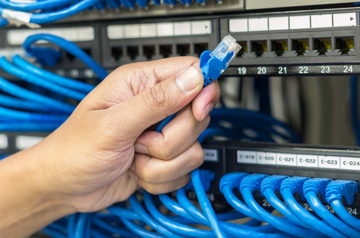 Hand holding cable in front of a server